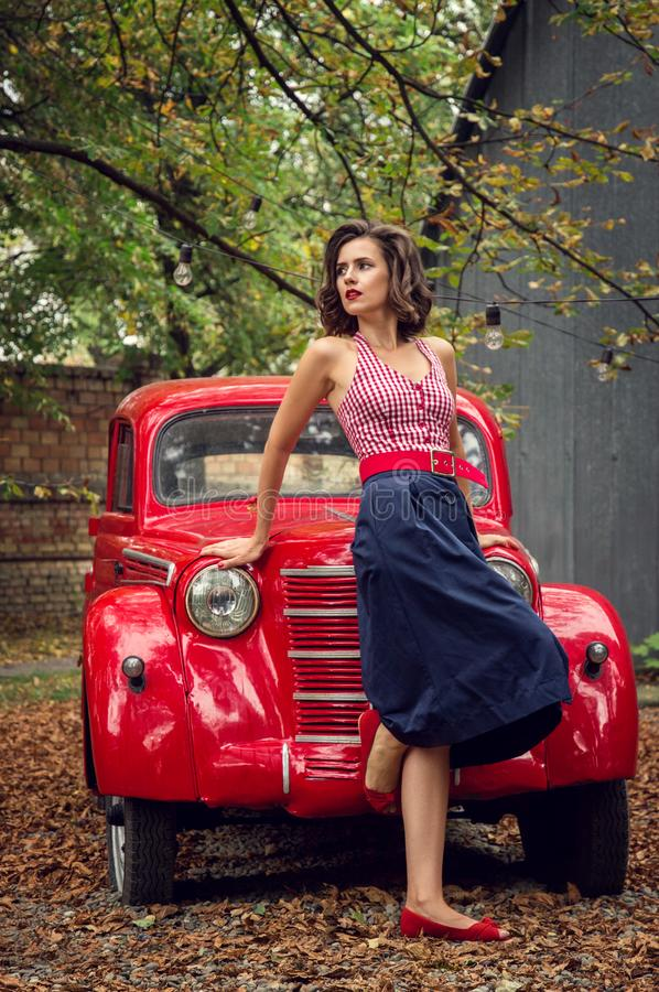 Pin-up girl posing on a red russian retro car background. A playful interested look is cast aside. The model is dressed in a red and white checkered top, wide royalty free stock image