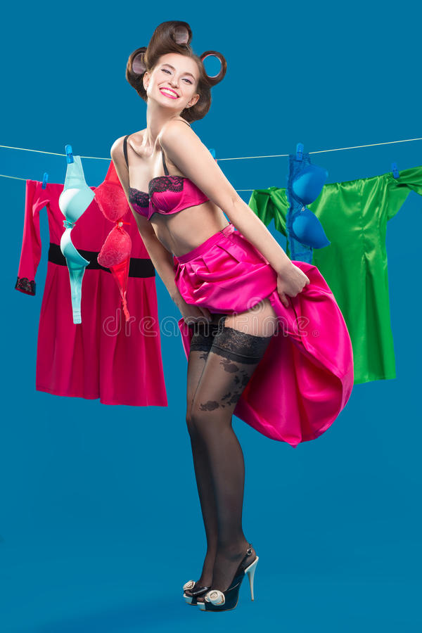 Pin-up girl on the ropes with the laundry. Pin-up girl on the background of the ropes with the laundry royalty free stock images