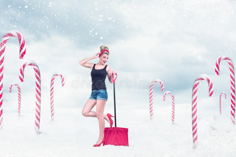 Pin-up girl with snow shovel royalty free stock images