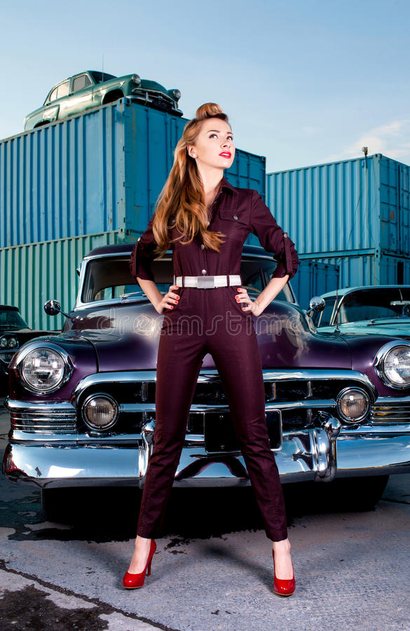 Pin-up girl standing near a retro car. Girl in pin-up on a background of retro cars. parking royalty free stock photo
