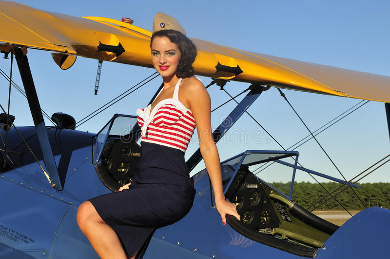 Pin up girl standing on a vintage biplane. 1940s pinup girl standing on a WWII biplane aircraft wing stock photos