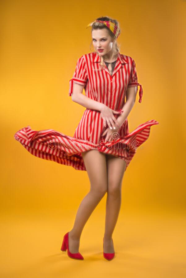 Pin-up girl in a striped dress. Classic soft focus. Flying hem of the dress. On a yellow background royalty free stock photos