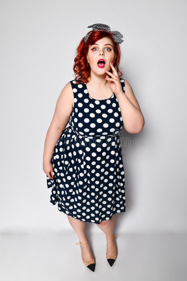 Pin up redhead woman . Beautiful retro female in polka dot dress with red lips and manicure nails and old fashion hairstyle. Beautiful full-length portrait of a royalty free stock image