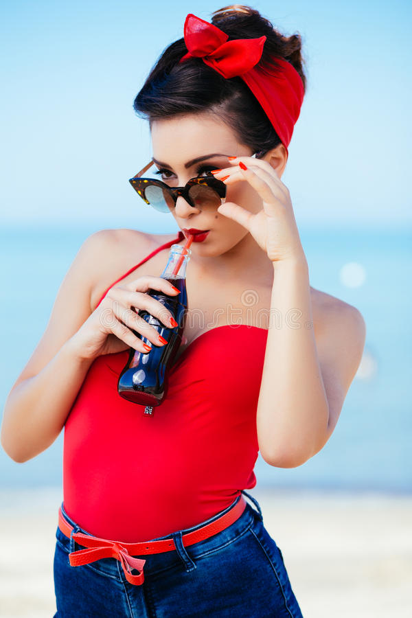 Pin-up at sea drink and watch over sunglasses royalty free stock photography