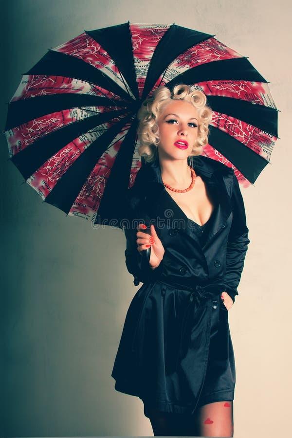 Pin-up. Stile americano. Donne in cappotto nero con l'ombrello immagini stock libere da diritti