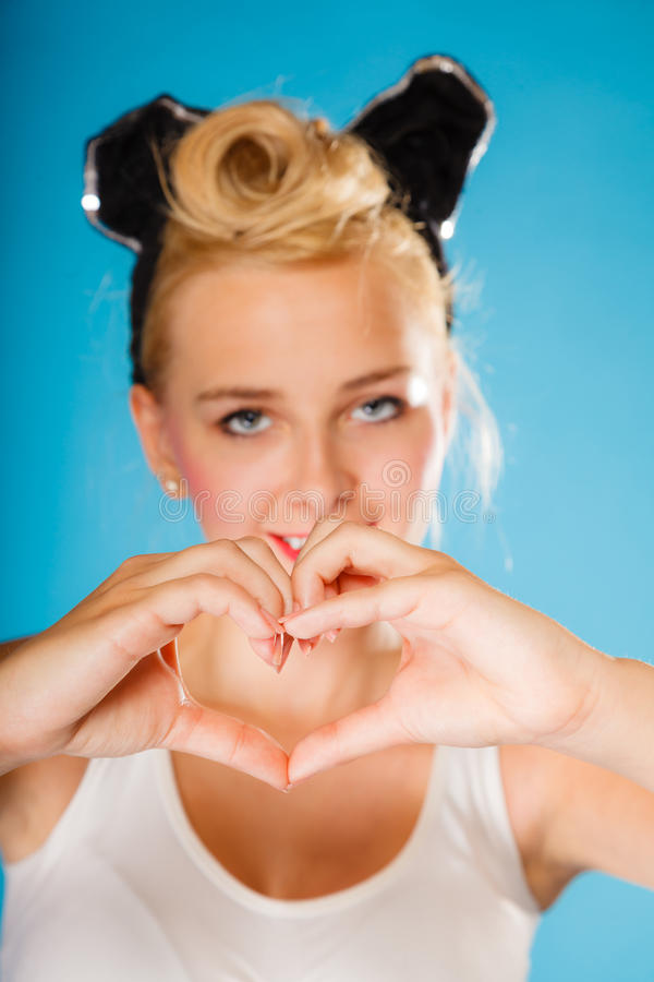 Pin up style, retro girl with heart sign. Pin up and retro style. Valentines day. Young smiling woman hairstyle making hands heart sign symbol on blue royalty free stock image