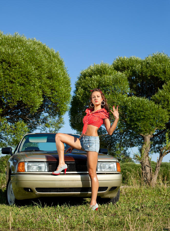 Pin-up style young woman stay before retro car royalty free stock photos