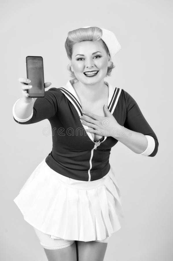 Pin-up styled girl with modern devices. Happy sea woman shows funny sms royalty free stock photo