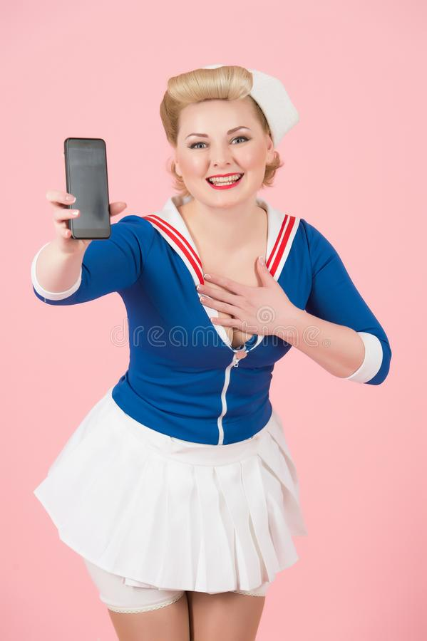Pin-up styled girl with modern devices. Happy sailor woman shows smart-phone and holds hand on chest. royalty free stock photography