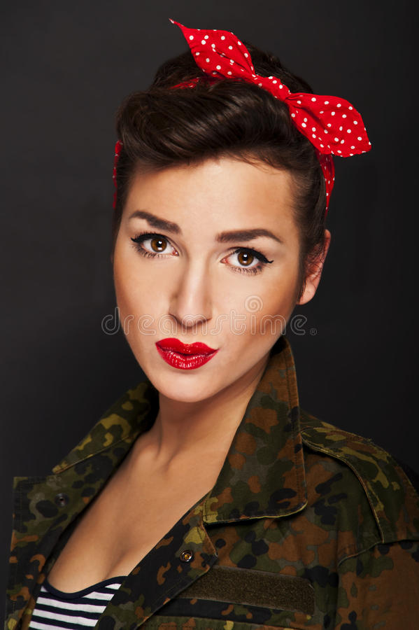 Pin-up woman with milytary jacket on black background. Kissing stock photos