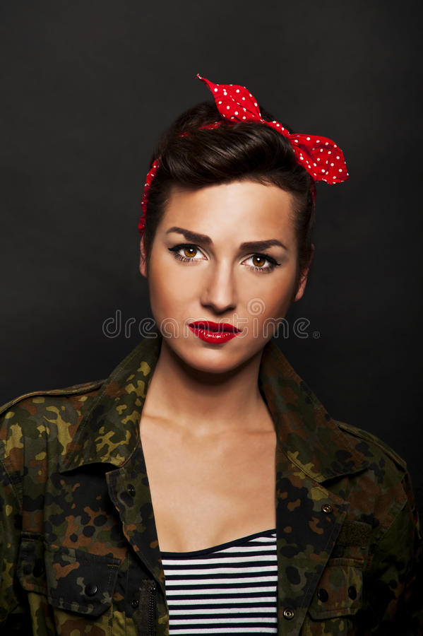 Pin-up woman with milytary jacket on black background. Kissing stock photo