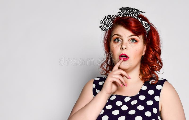Pin up redhead woman. Beautiful retro female in polka dot dress with red lips and manicure nails and old fashion hairstyle. Pin up woman portrait. Beautiful stock image