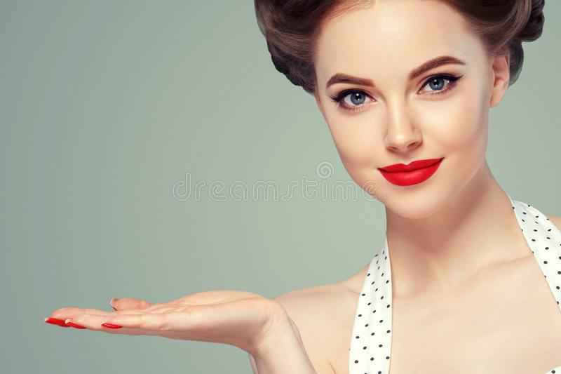 Pin up woman portrait. Beautiful retro female in polka dot dress with red lips and manicure nails and old fshion hairstyle hand royalty free stock photography