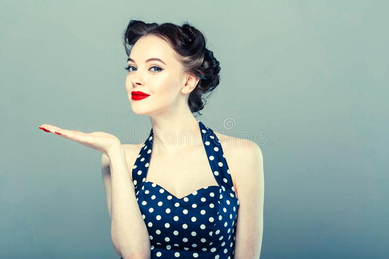 Pin up woman portrait. Beautiful retro female in polka dot dress with red lips. Studio shot stock images