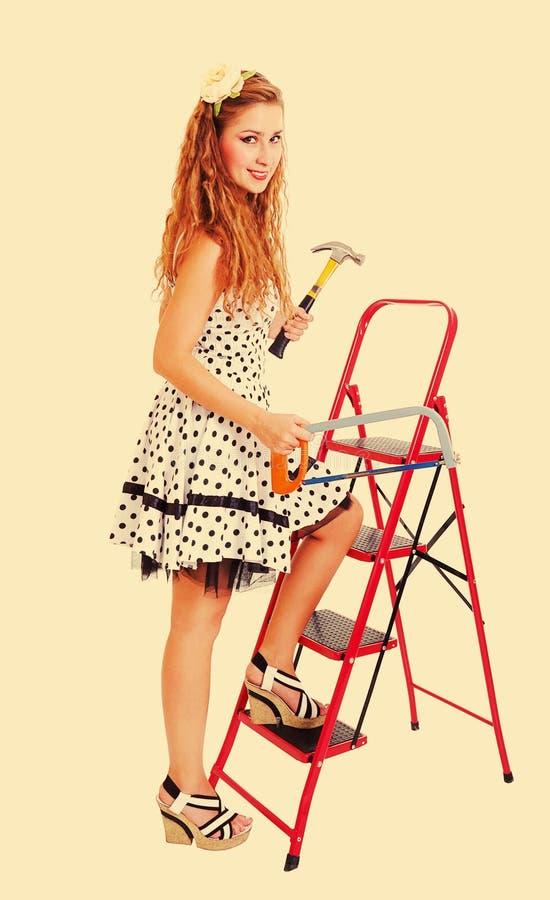 Pin vers le haut de femme sur l'échelle avec un marteau, modifié la tonalité image libre de droits