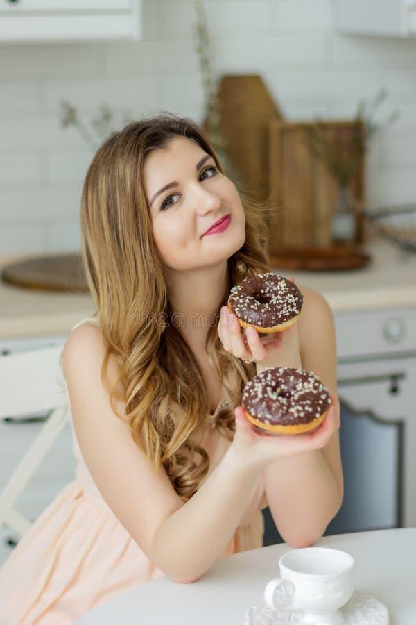 Pin vers le haut de la fille mangeant avec émotion jugeant deux butées toriques dans la cuisine à la table image stock