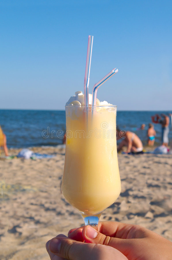 Pina-colada cocktail on the beach in woman hand stock photos