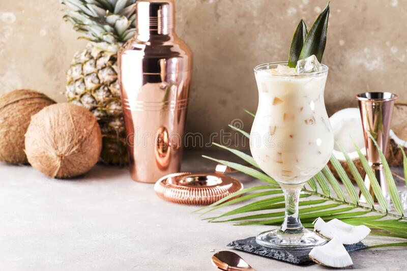 Pina Colada Cocktail on sand beige background with tropical fruits and bar tools, summer relaxation concept, copy space royalty free stock image