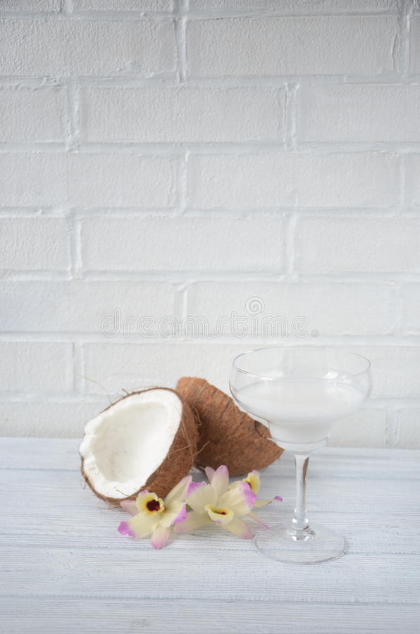 Download Pina Colada Drink In Cocktail Glass Decorated With Coconut And Orchid Flowers Stock Photo - Image: 83700924