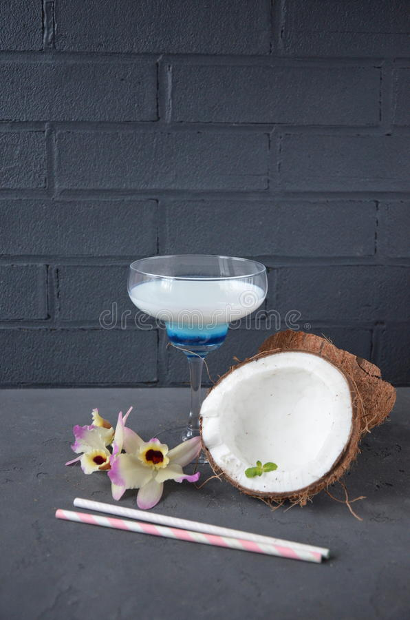 Download Pina Colada Drink In Cocktail Glass Decorated With Coconut And Orchid Flowers Stock Photo - Image: 83701203
