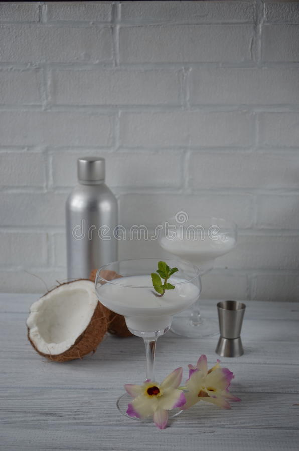 Download Pina Colada Drink In Cocktail Glass Decorated With Coconut And Orchid Flowers Stock Photo - Image: 83701625