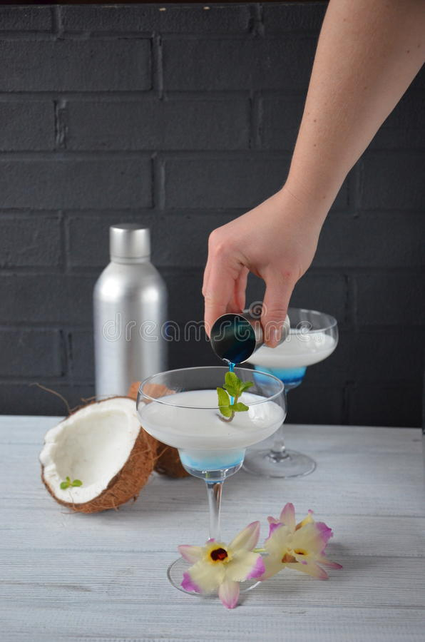 Download Pina Colada Drink In Cocktail Glass Decorated With Coconut And Orchid Flowers Stock Photo - Image: 83701672