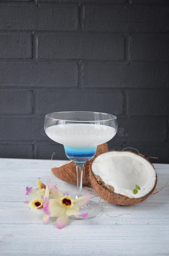 Download Pina Colada Drink In Cocktail Glass Decorated With Coconut And Orchid Flowers Stock Photo - Image: 83701793