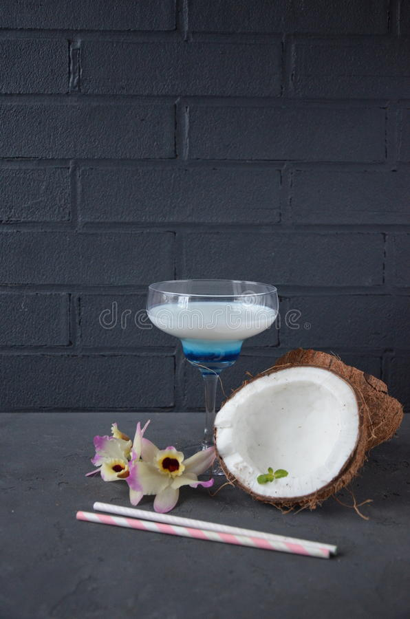 Download Pina Colada Drink In Cocktail Glass Decorated With Coconut And Orchid Flowers Stock Photo - Image: 83701835