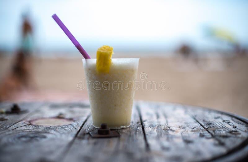 pinacolada玻璃在桌上的在海滩 库存照片