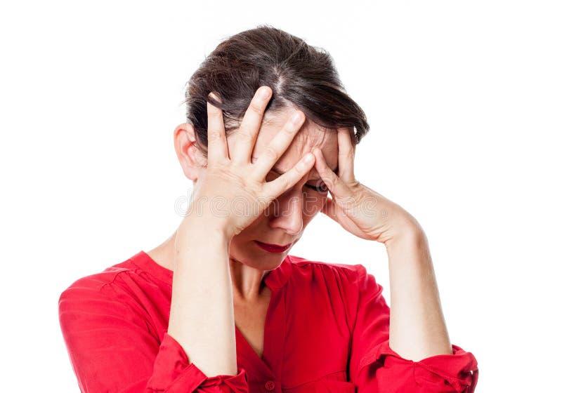 Pinad ung kvinna som trycker på hennes panna med ångest arkivfoto