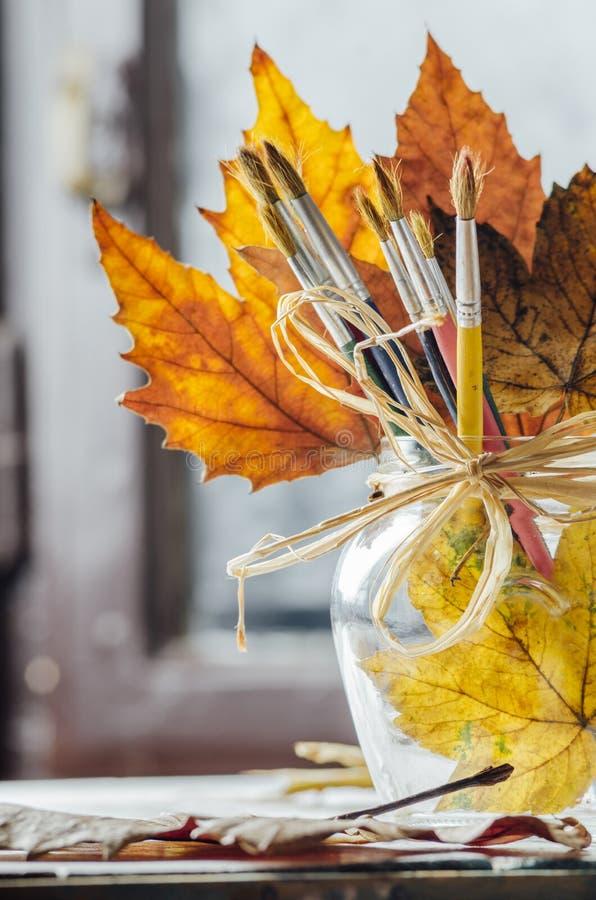 Pincéis da arte e folhas de outono fotografia de stock