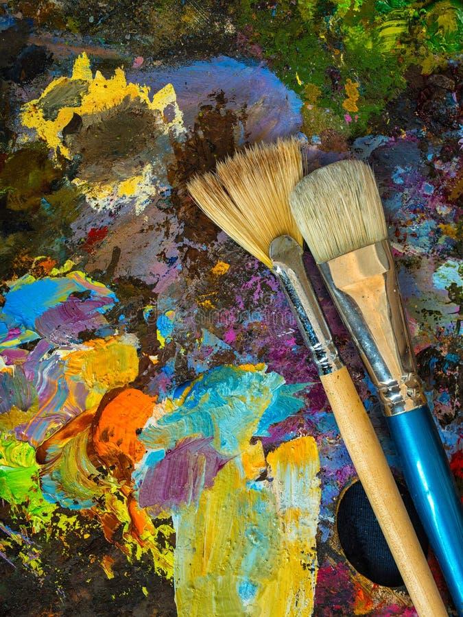 Pincéis na paleta para pinturas de óleo de mistura foto de stock royalty free