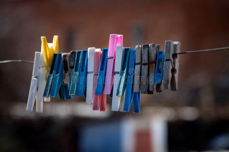 Pince à linge colorée accrochant sur une corde Pinces à linge en plastique et en bois photographie stock