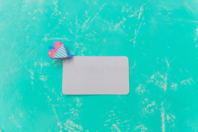 Pince à linge colorée avec la conception de forme de coeur et la feuille de livre blanc carte de valentine d'isolement sur le fon photo stock