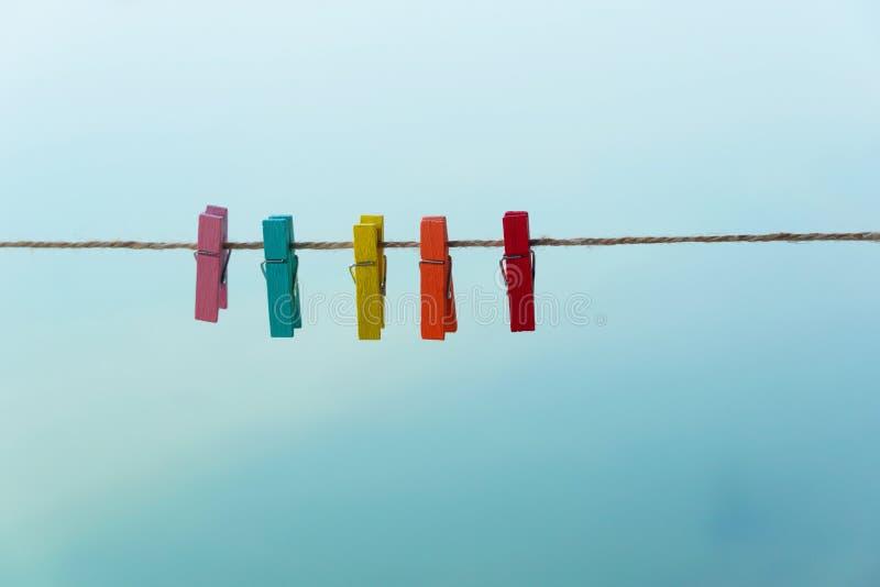 Pince à linge colorée ou agrafe en bois avec le fond de corde naturelle et de ciel bleu photo stock