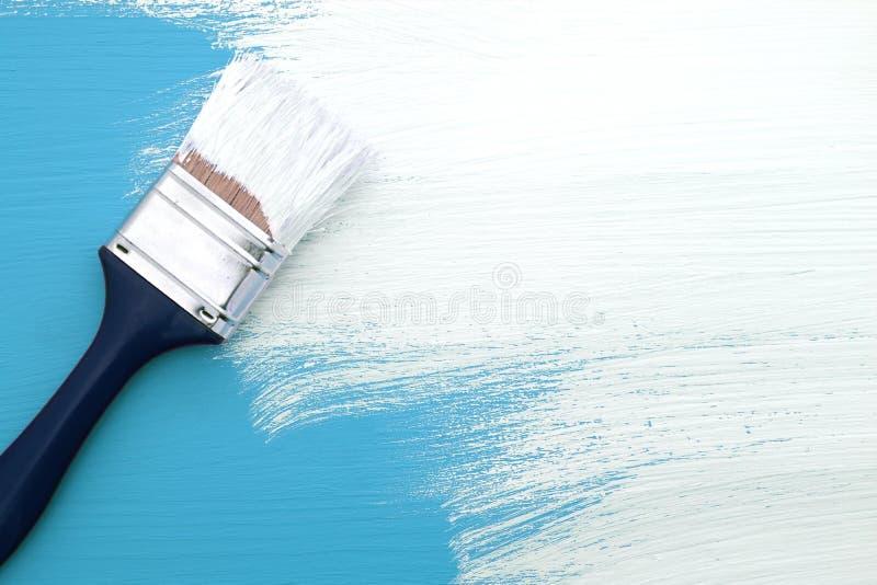 pinceau avec la peinture blanche peignant au dessus du. Black Bedroom Furniture Sets. Home Design Ideas