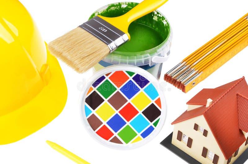 Pinceau sur des boîtes avec des impressions couleur, modèle de maison, casque, vue supérieure sur un fond blanc photo stock