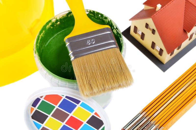 Pinceau sur des boîtes avec des impressions couleur, modèle de maison, casque, vue supérieure sur un fond blanc photos libres de droits