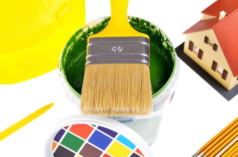 Pinceau sur des boîtes avec des impressions couleur, modèle de maison, casque, vue supérieure sur un fond blanc image libre de droits