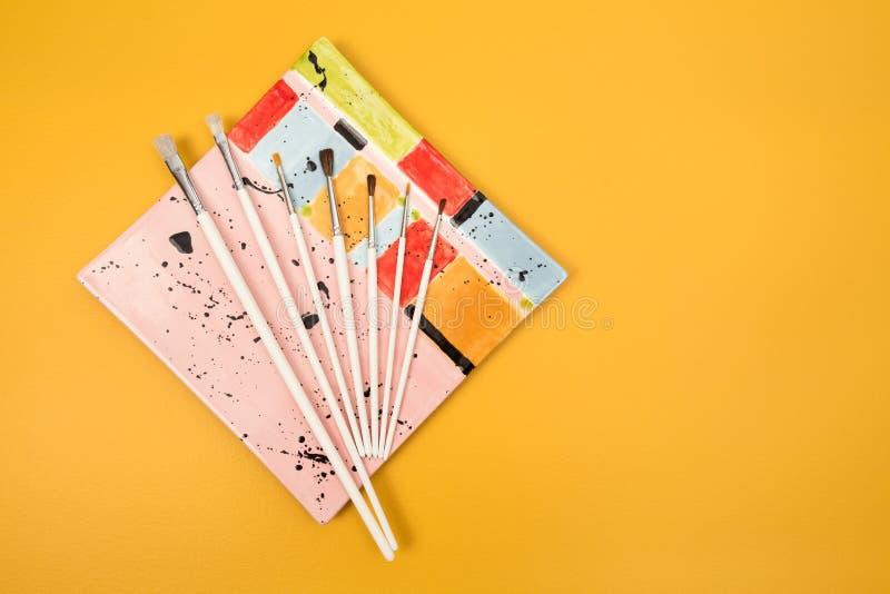 Pinceaux blancs d'un plat en céramique coloré photographie stock