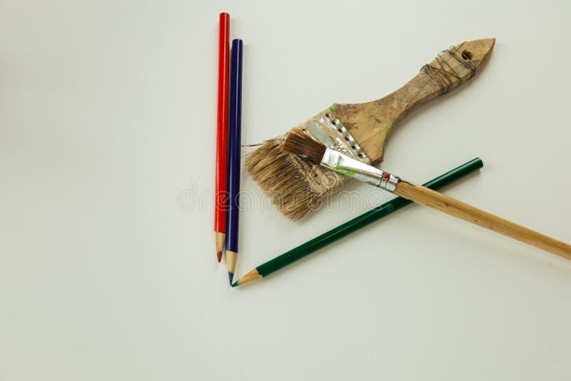 Pinceaux d'outils d'artiste colorant des crayons sur le fond solide images stock