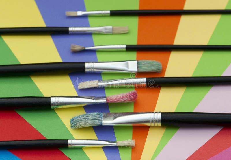 Pinceaux et papier coloré photo stock