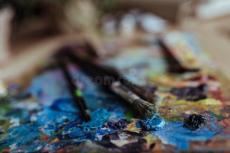 Pinceaux sur la palette utilisée pendant le travail créatif photos stock