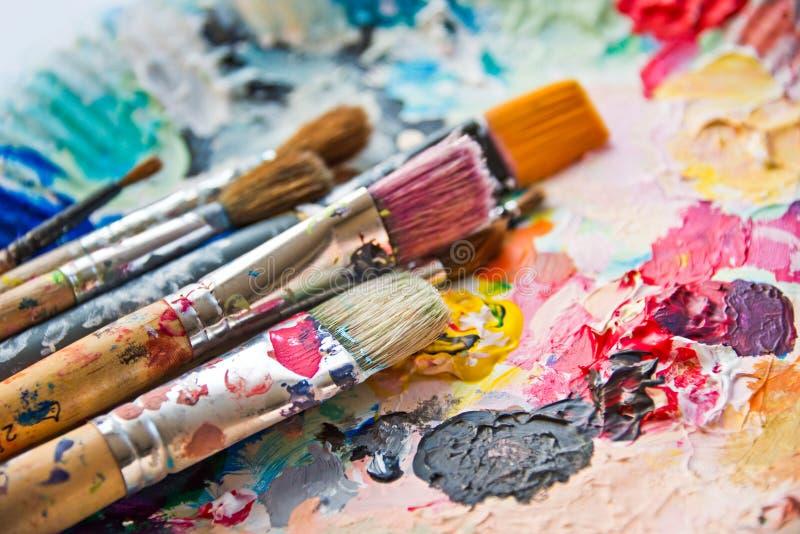 Pinceaux utilisés sur une palette colorée images stock