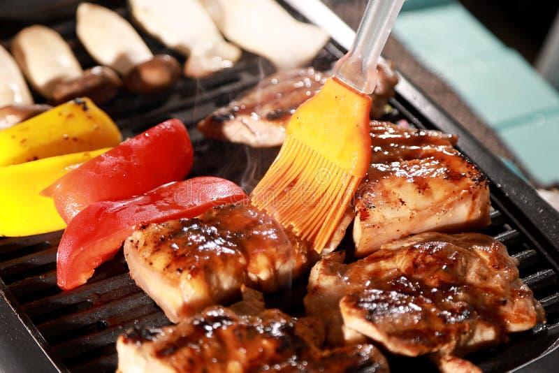 Pincel de molho de churrasco com fumaça e Barbecue Pork, tomate, pimenta amarela, cogumelo no churrasco fotos de stock