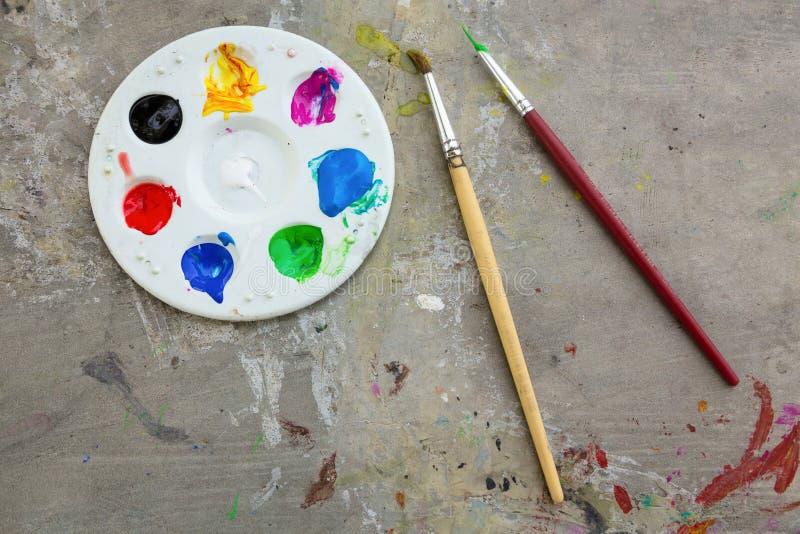 Pincel e pintura da aquarela, paletas na mancha da tabela o objeto da cor, da educação e da arte, vista superior foto de stock