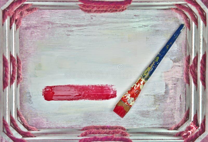 Pincel na caixa de madeira branca, única listra vermelha de pintura fotografia de stock royalty free