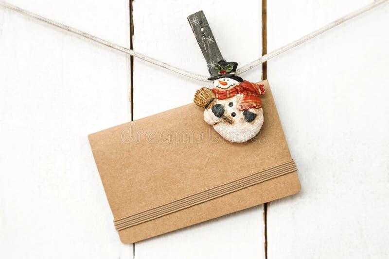 Pinces à linge de bonhomme de neige de Noël tenant la carte de voeux photo stock