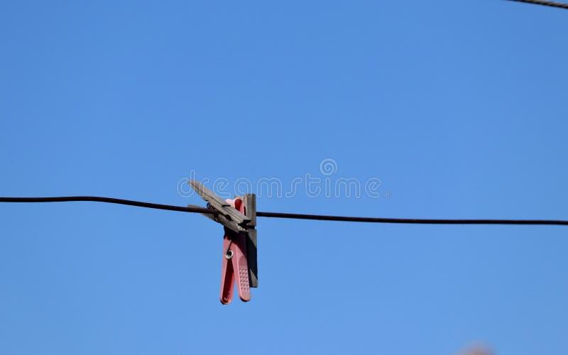 Pinces à linge de pinces à linge sur un fil en métal contre le ciel bleu clair vif image libre de droits