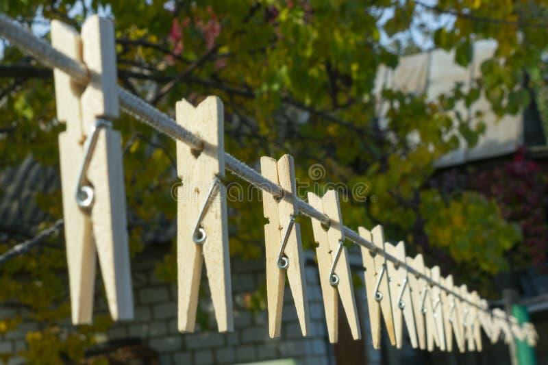 Pinces à linge en bois sur une corde pesant dans la perspective, pendant l'automne, photo stock